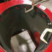 a red Vertical Unload Auger tube liner with Cast elbow in a work shop