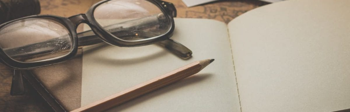 desk with glasses, a pencil, and an open notepad